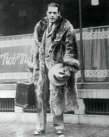 "05 Dec 1925, Philadelphia, Pennsylvania, USA --- Here's a pose of Harold ""Red"" Grange, the Nation's football idol, as he appeared on his arrival in Philadelphia with the Chicago Bears, the professional football team which he joined after playing his last collegiate game. Grange was, for the first time, pictured in street attire and seems a little like the phantom of the gridiron in his heavy raccoon skin coat. --- Image by © Bettmann/CORBIS"